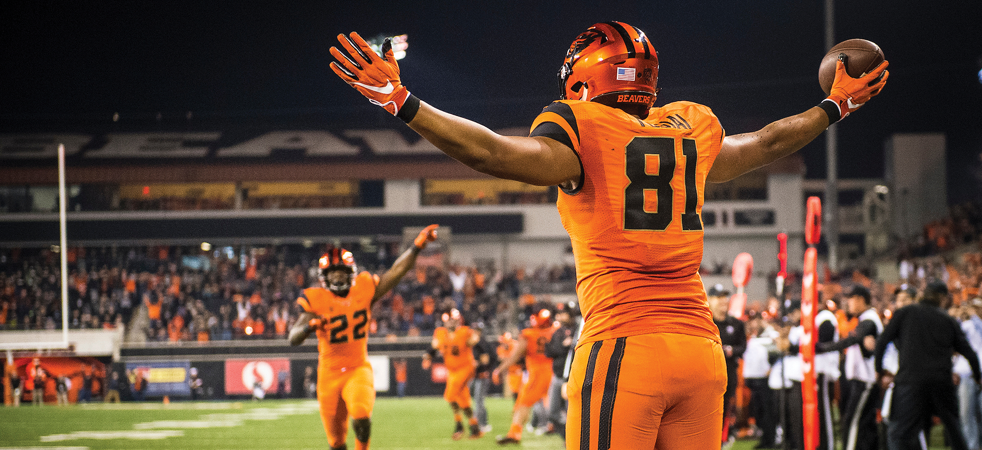 Football player on a football field during a game in orange jersey with back facing camera. His arms are raised up and it's night time.