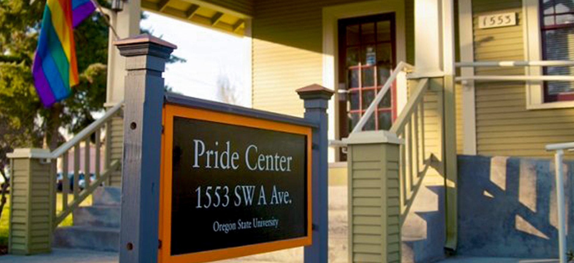 A sign with Pride Center and 1553 SW A. Ave in front of a home with a pride flag.