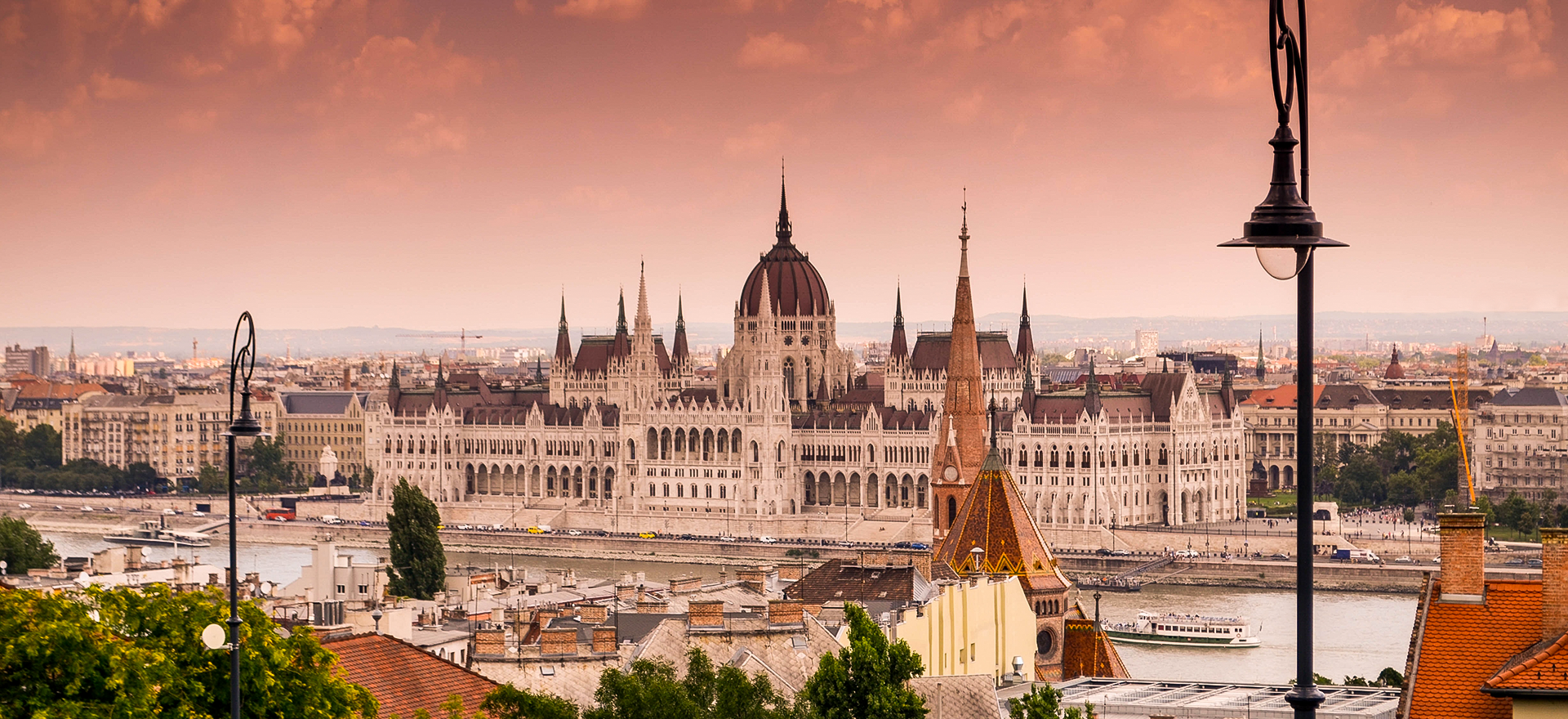 Budapest, Hungary at sunset. A white cathedral building along a river.