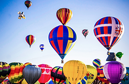 A group of about 30 vibrant hot air balloons crowd together on the ground and in the air against a clear, blue sky.