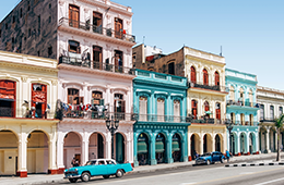 Cuba colorful buildings with old fashioned cars