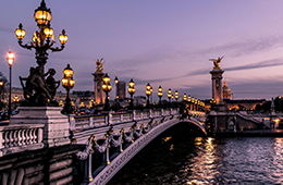 Paris bridge covered in lampposts with river below at sunset